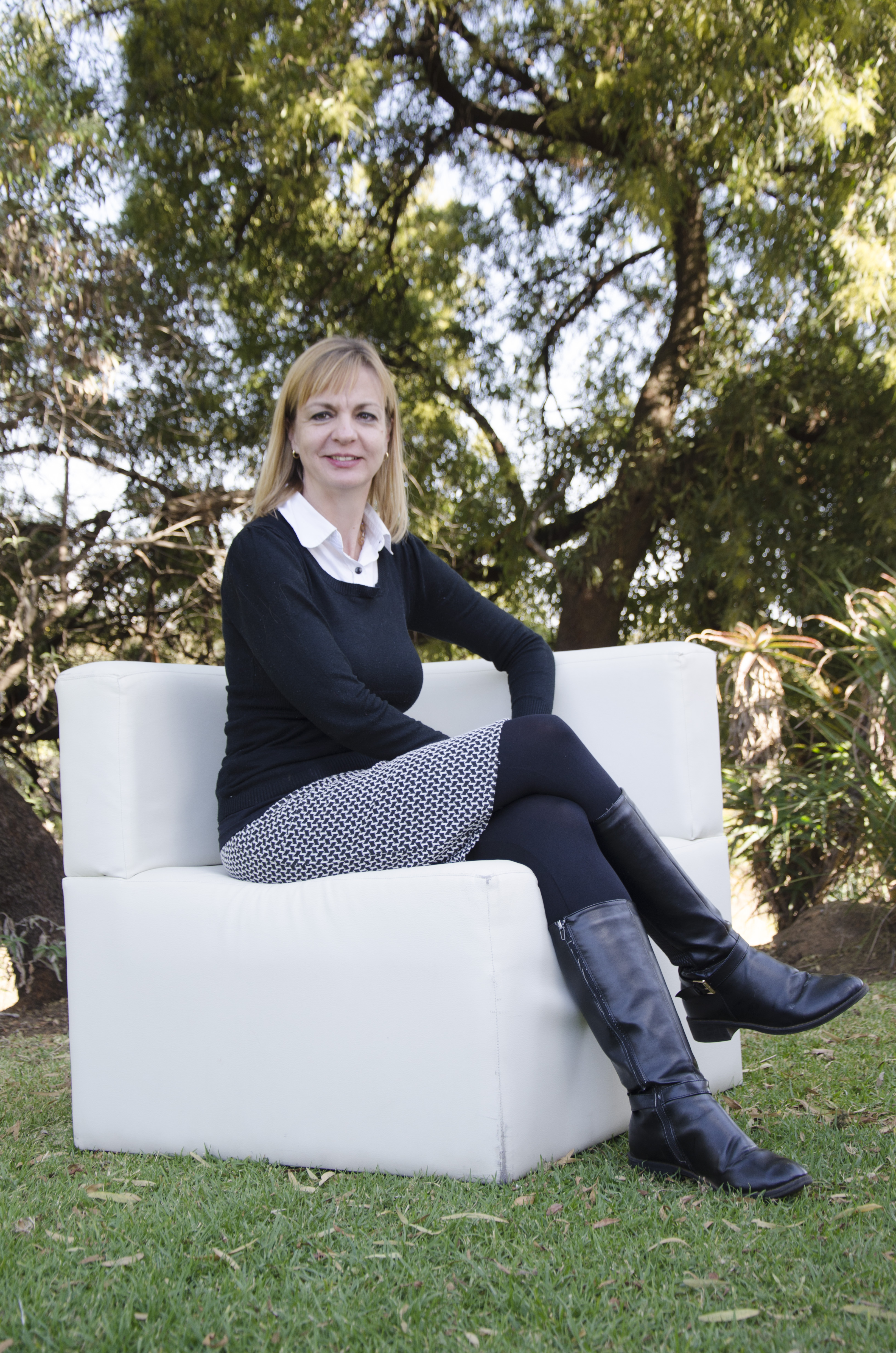 Photograph of Irma Karsten sitting outside on a white couch under the trees. Irma is wearing a navy blue pullover and a white collared top.